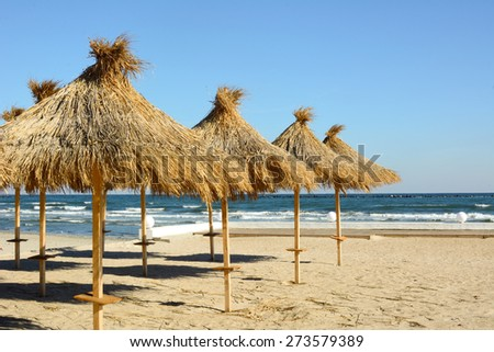 Reed umbrellas on the beach to the seaside - stock photo