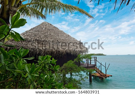 Reef Bungalows over tropical coral reef in tropical pacific ocean Island. - stock photo