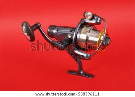Reel for fishing rods, close up on red background