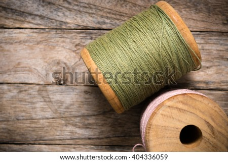 Reel pink with green yarn right side on wood background - stock photo