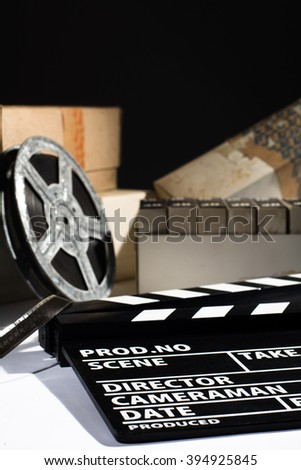 Reel with film and cinema clap. Old film in boxes - stock photo