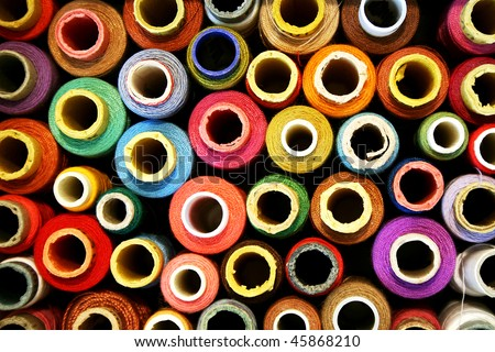 reels of color threads on black - stock photo