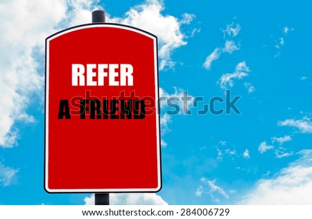 Refer a Friend motivational quote written on red road sign isolated over clear blue sky background. Concept  image with available copy space