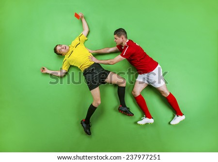 Referee giving red card to a football player. Studio shot on a green background. - stock photo