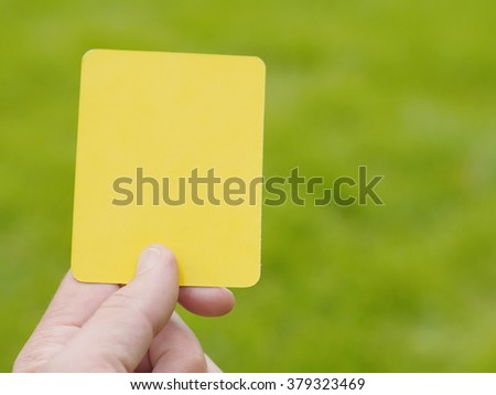 referee hand with yellow card - stock photo