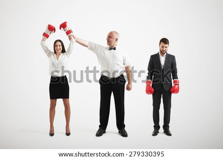 referee holding happy winner businesswoman in boxer gloves and looking at her, near standing sad loser businessman over light grey background - stock photo