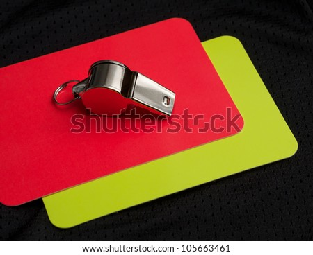 Referee red card and whistle - stock photo