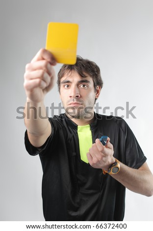 Referee showing a yellow card - stock photo