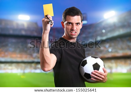 Referee showing the yellow card in the soccer stadium.
