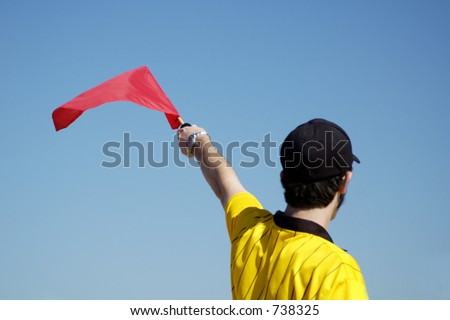 Referee signaling from the sidelines of a soccer game. - stock photo