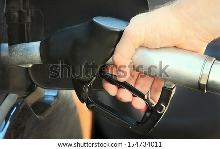 Refilling the car with unleaded petrol - stock photo