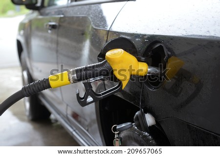 refilling up gas tank of the car with green eco fuel on a filling station - stock photo