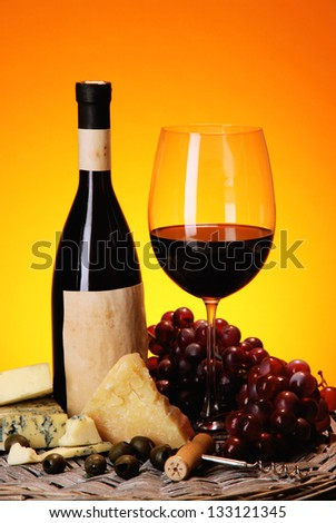 Refined still life of wine, cheese and grapes on wicker tray on wooden table on orange background - stock photo