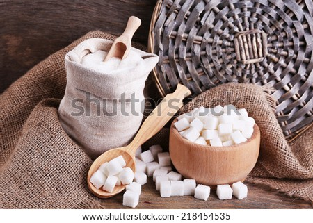 Refined sugar in bag and bowl on wooden background - stock photo