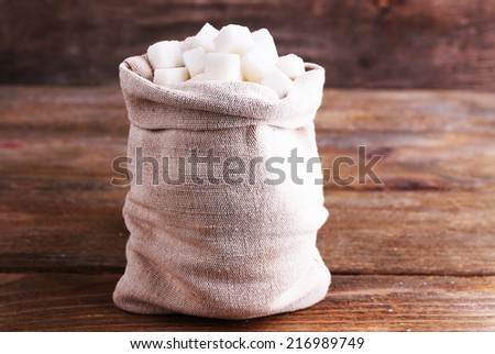 Refined sugar in bag on wooden background - stock photo