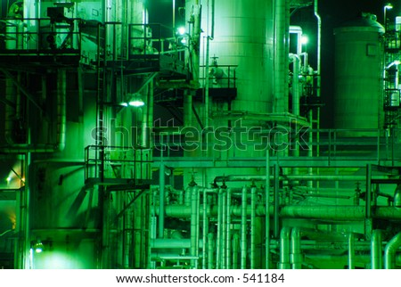 Refinery at night - detail of pipes lit my mercury vapor lights - stock photo