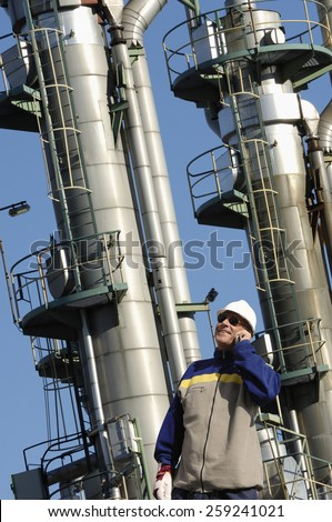refinery details, worker and fuel towers inside refinery - stock photo