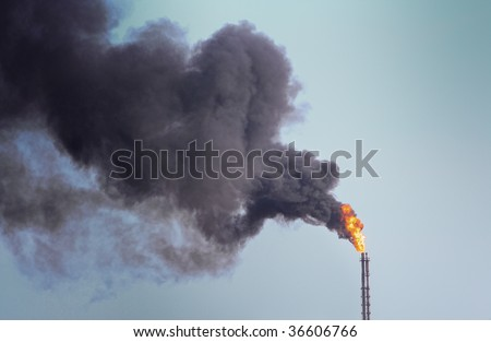 Refinery funnel burning with huge flame and throwing clouds of dark smoke - stock photo