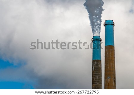 Refinery Smoke stacks spilling out smoke. Purging before they produce  - stock photo