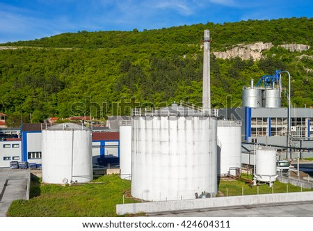 Refinery. The office building of the plant. Metal containers for storage of crude oil  - stock photo