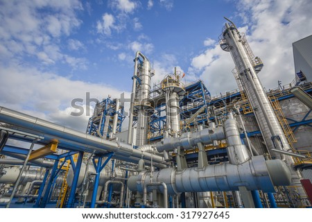 Refinery tower in petrochemical industrial plant with cloudy sky - stock photo