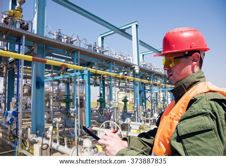 Refinery worker in front of natural gas storage