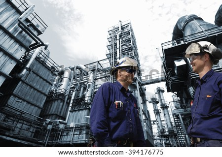 refinery workers in close-ups with large oil and gas industry in background - stock photo