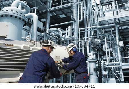 refinery workers inside large oil and gas installation - stock photo