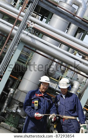refinery workers with large pipelines and towers in background - stock photo