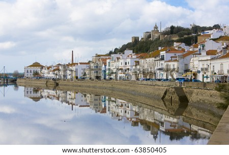 Reflected view over Alcacer do Sal, a typical village on the margins of the Sado river, Setubal, Portugal - stock photo