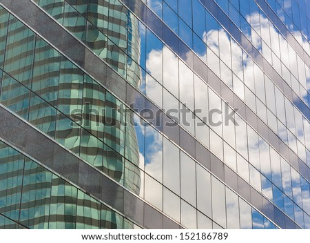 reflected windows of modern office building and blue sky