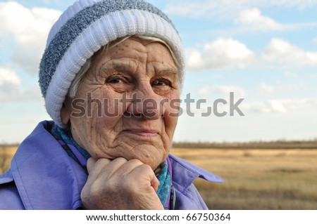 Reflecting, an elderly woman looks away, the background road, autumn - stock photo
