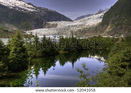 Reflecting pine trees in the foreground of the Mendenhall Glacier in Juneau, Alaska. - stock photo