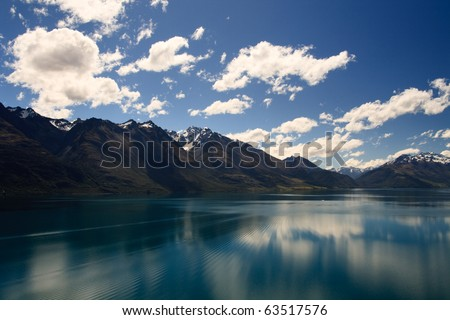 Reflection from Lake Wakatipu surrounded by mountains near Queenstown, South Island, New Zealand - stock photo