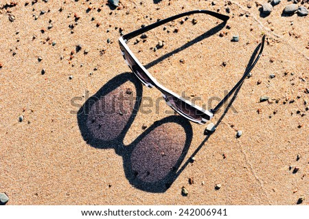 Reflection from plastic sunglasses in the sand