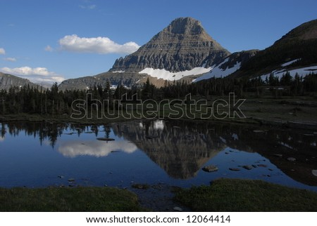 Reflection in a mountain lake in Glacier - stock photo