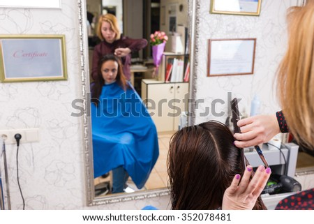 Reflection in Large Mirror of Young Blond Stylist Combing Hair of Brunette Client Wearing Blue Smock in Hair Salon