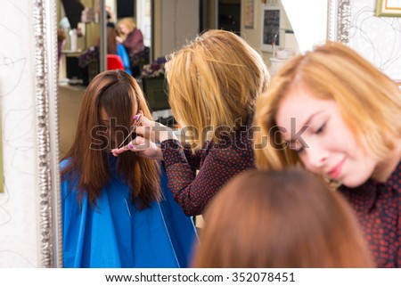 Reflection in Large Salon Mirror of Young Blond Stylist Cutting Hair of Brunette Client - Hair Stylist Trimming Bangs for Customer