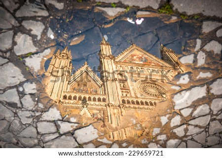 Reflection in puddle of water the cathedral in Orvieto, Umbria - stock photo