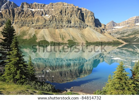 Reflection in smooth water of mountain lakes (Banff National Park, Alberta, Canada) - stock photo