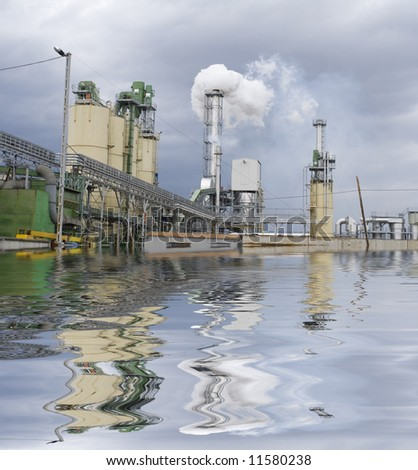 Reflection in the lake of large chemical factory - stock photo