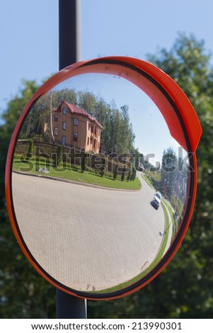 reflection in the mirror of the road from a stone blocks at the house, lawn and woods - stock photo