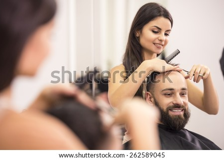 Reflection in the mirror woman hairdresser is cutting man hair. - stock photo