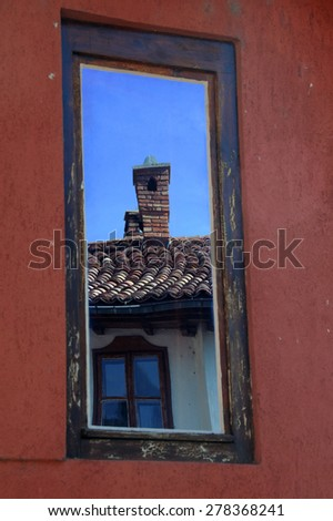 Reflection in the shabby wall window of the old house - stock photo