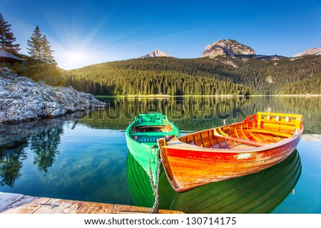 Reflection in water of mountain lakes and boats. Black lake in Durmitor national park in Montenegro, Europe. Beauty world. - stock photo