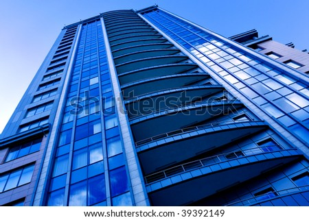 Reflection in windows of bright blue sky - stock photo