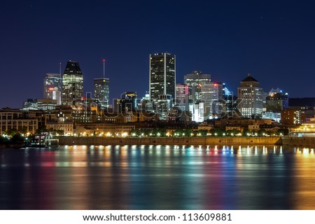 Reflection light in the water, in front of port of Montreal, and downtown in background at night. - stock photo