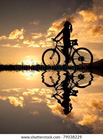 Reflection mountain biker Woman silhouette - stock photo