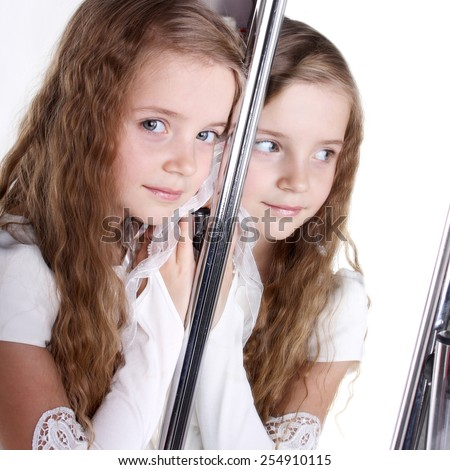 reflection of a beautiful little girl in the mirror