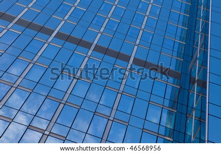 Reflection of a clear blue sky in a glass office building